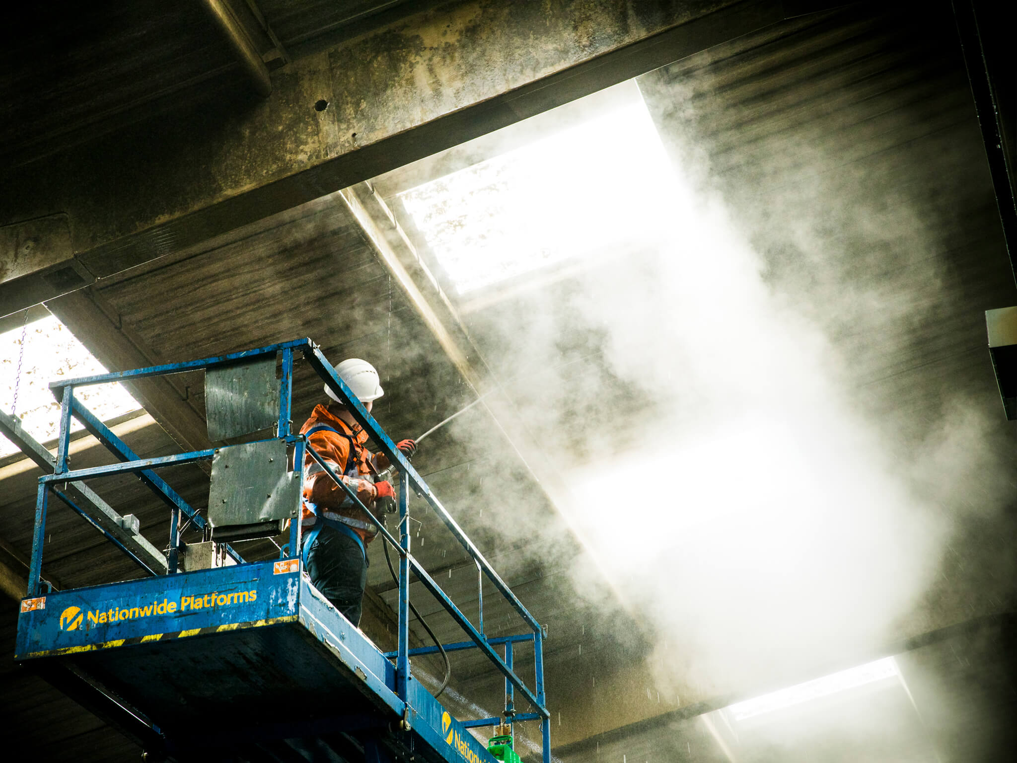 Technician on Scissor Lift Cleaning Warehouse Ceiling